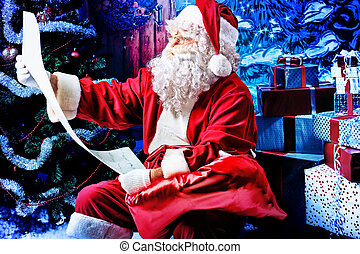 list of presents - Santa Claus posing with a list of...