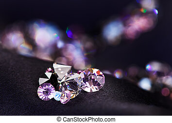 Diamond small purple jewel stones heap over black silk cloth...