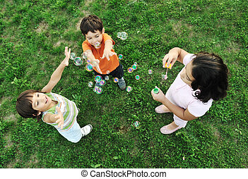 Small group of happy children making bubbles and playing...
