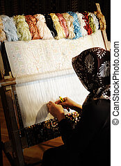 Woman working at the loom. Oriental Muslim national crafts....