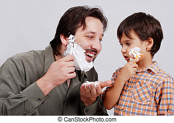 Man in bathroom putting shaving cream on young boys face