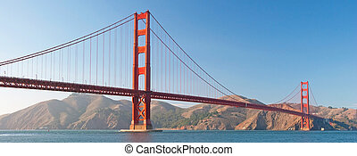 The Golden Gate Bridge in San Francisco during the sunset with beautiful azure ocean in background panorama