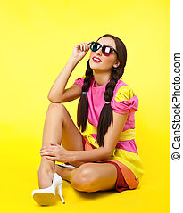 Cute girl like doll dress look in stereo glasses on yellow...