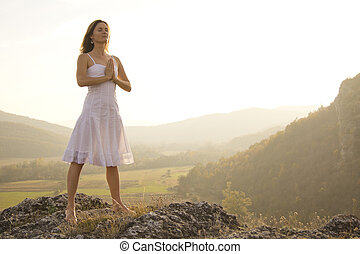 Stability - Young woman standing in meditation on the top of...