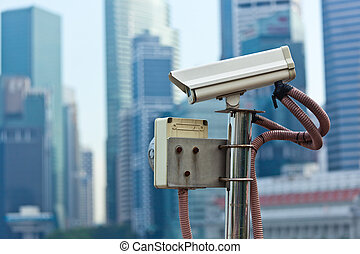 CCTV surveillance camera in Singapore with skyscapers in...