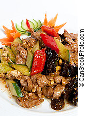 Roasted pork with vegetables on a plate isolated on white...