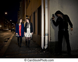 Stalking man - Hooded man stalking two women behind a corner...