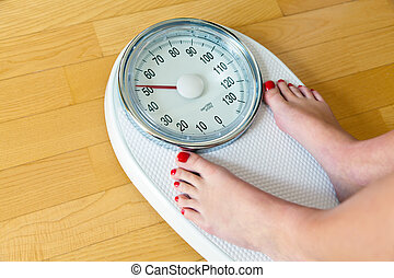 feet of a woman on bathroom scales - the feet of a woman...