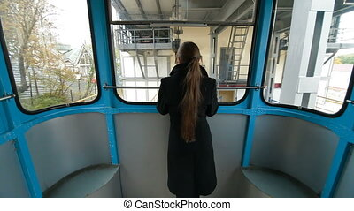Passenger in cabin the cable car - young woman in the cabin...