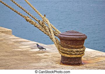Rusty mooring bollard with ship ropes on Zadar docks