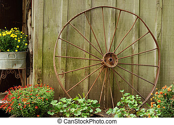 old wagon wheel leaning on barn with flowers