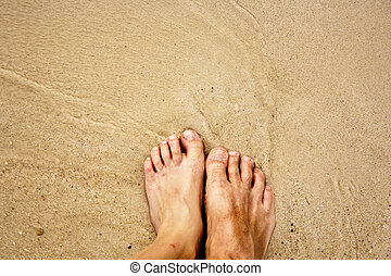 feet of a man in the fine sand surrounded by saltwater -...