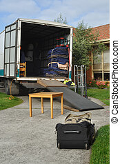 Relocation truck loaded with furniture, table, briefcase,...