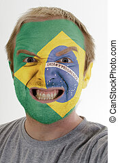 Face of crazy angry man painted in colors of brazil flag