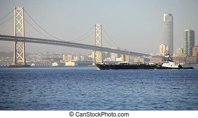 Tugboat at Bay Bridge - Oakland Bay Bridge with a ship and...