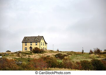 yellow house on hill - yellow house upon a grassy hill in...