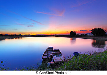 Sunset along the pond with two boats