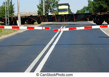 Freight train passing a railroad crossing with gates