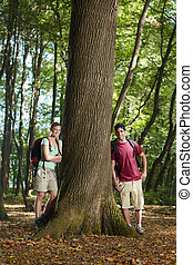 environmental conservation: young hikers leaning on tree -...