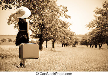 Lonely girl with suitcase at countryside