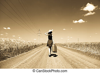 Lonely girl with suitcase at country road. Photo in old...