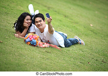 couples self portrait - ypung couples laying on grass and...