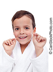 Little boy flossing teeth