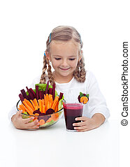 Little girl with fresh vegetables and juice