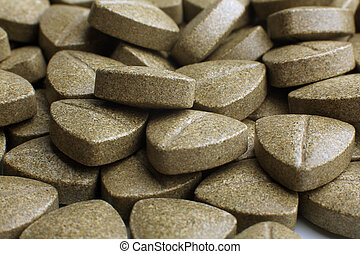 Heap of grassy tablets on a white background