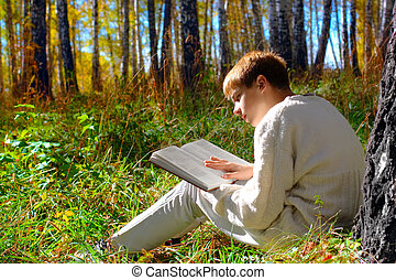 boy reading - reading boy sit in autumn forest with a book
