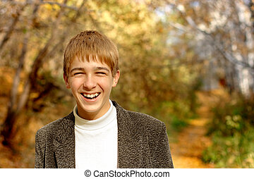 laughing teenager - laughing boy stand in autumn forest