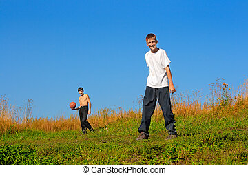 boys outdoor - Happy teenagers play a ball on a field