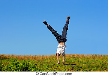 boy stand on arms - Somersault on grass on the blue sky...