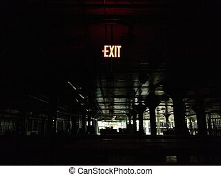 Exit - Illuminated exit sign in a dark empty warehouse