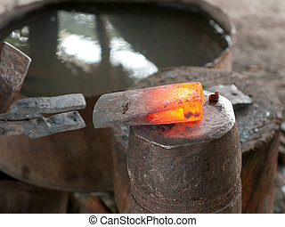 Red hot head of ax at a blacksmith's workshop