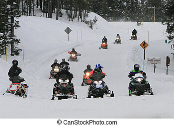 Snowmobile road - Snowmobile riders return after a day of...