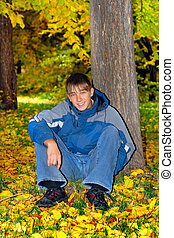 teenager in the park - smiling teenager sitting in autumn...