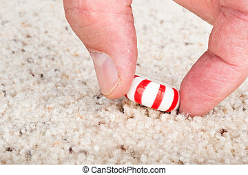 Candy stuck to carpet - A person pulling a sticky candy mint...