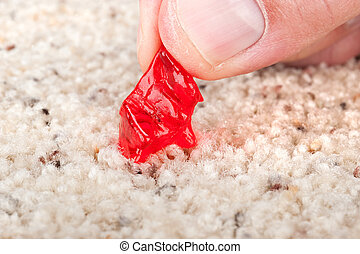 Candy stuck on carpet - A person pulling a chewy, gummy...