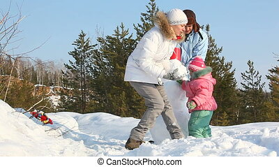 Making a snowman - Family of three spending time outdoors...