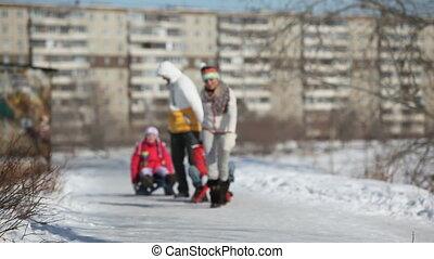 Urban sledge ride - Parents giving their children a sledge...