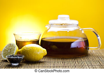 Glass teapot and cup with tea, lemon