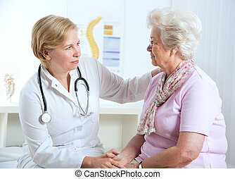 senior woman visiting a doctor - female doctor explaining...