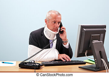 Injured businessman at his desk on the phone - Photo of a...