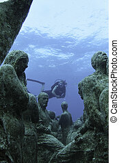 diver at underwater museum - A diver examines the underwater...