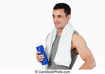 Young man with a bottle after workout