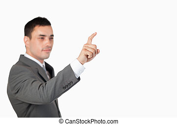 Businessman using invisible touchscreen against a white...