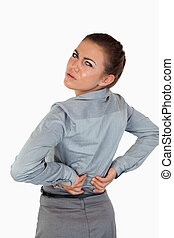 Portrait of a young businesswoman having back pain