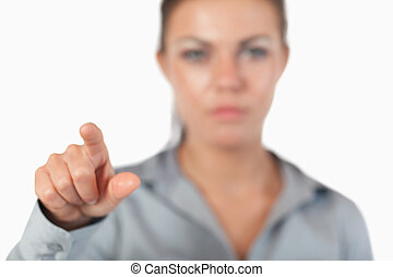 Young businesswoman pressing an invisible key with the...
