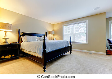 Large beige bedroom with lare dark bed. Interior.